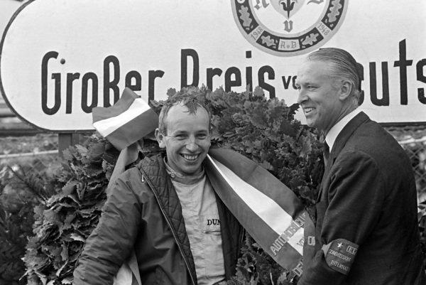 John Surtees celebrates his maiden victory on the podium.