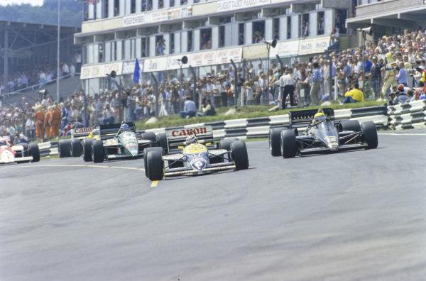 Nelson Piquet, Williams FW11 Honda, battles with Ayrton Senna, Lotus 98T Renault.