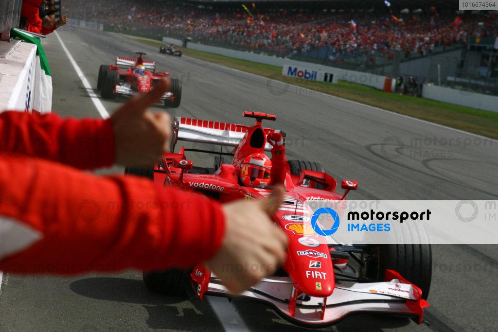 Michael Schumacher and Felipe Massa, Ferrari 248 F1, celebrate a Ferrari 1-2 as they pass their team on the pitwall.