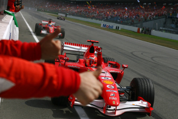 Michael Schumacher and Felipe Massa, Ferrari 248 F1, celebrate a Ferrari 1-2 as they pass their team on the pitwall.