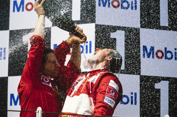 Michael Schumacher, 1st position, celebrates securing his fifth world drivers' championship on the podium with Jean Todt.