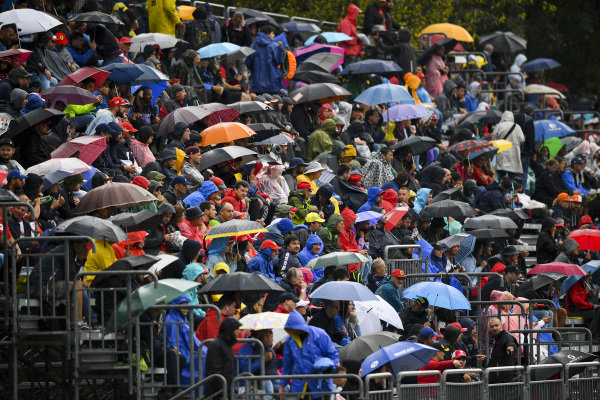 Fans in the grandstand with umbrellas in the rain