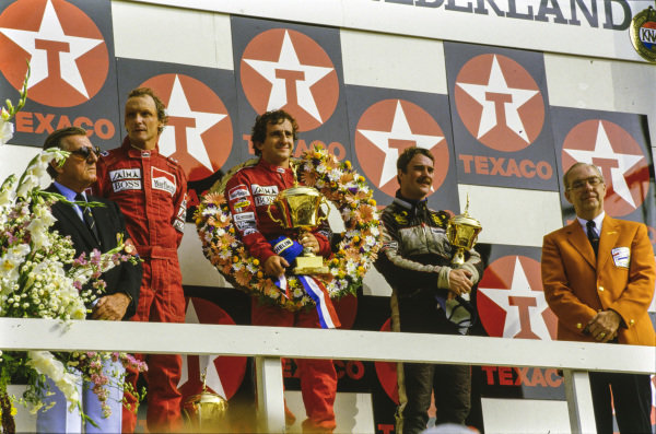 Alain Prost, 1st position, Niki Lauda, 2nd position, Nigel Mansell, 3rd position, and FIA/FISA President Jean-Marie Balestre on the podium.