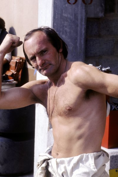 Mike Hailwood (GBR), McLaren, shows off his muscles to the camera in his final season as a Grand Prix driver. 1974 Formula One World Championship.