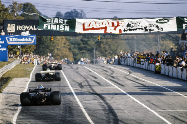 Race winner James Hunt, McLaren M23, leads ninth placed Ronnie Peterson, March 761, and second placed Patrick Depailler, Tyrrell P34, past the start/finish line to complete another lap.