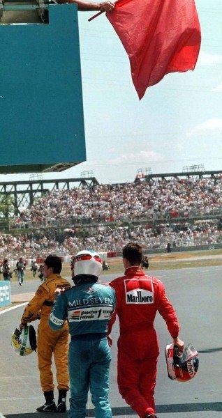 1997 Canadian Grand Prix.Montreal, Quebec, Canada.13-15 June 1997.Michael Schumacher (Ferrari), Jean Alesi (Benetton Renault) and Giancarlo Fisichella (Jordan Peugeot) walk beneath the red flag that halted the race prematurely.World Copyright - LAT Photographic