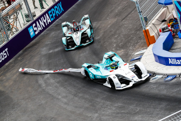 Tom Dillmann (FRA), NIO Formula E Team, NIO Sport 004, with an advertising banner stuck to his car, leads Mitch Evans (NZL), Panasonic Jaguar Racing, Jaguar I-Type 3
