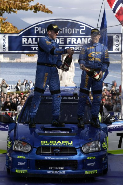 2003 FIA World Rally Champs. Round Twelve Corsica Rally 16th-19th October 2003.Petter Solberg and co-driver Phil Mills celebrate on the podium, Subaru, Pordium World Copyright: McKlein/LAT