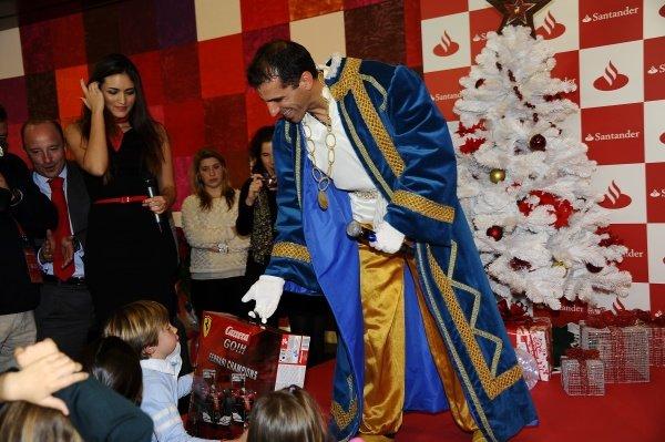 Marc Gene (ESP), Ferrari test driver, hands out presents to children.Santander Christmas Festivities, Madrid, Spain, Monday 19 December 2011. *** Local Caption *** RUBIO