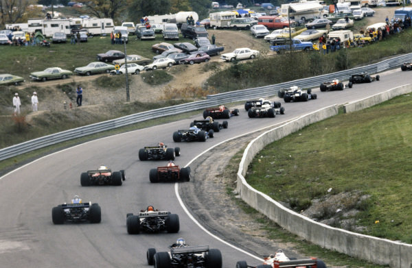 The field of cars speed up the hill on lap 1.
