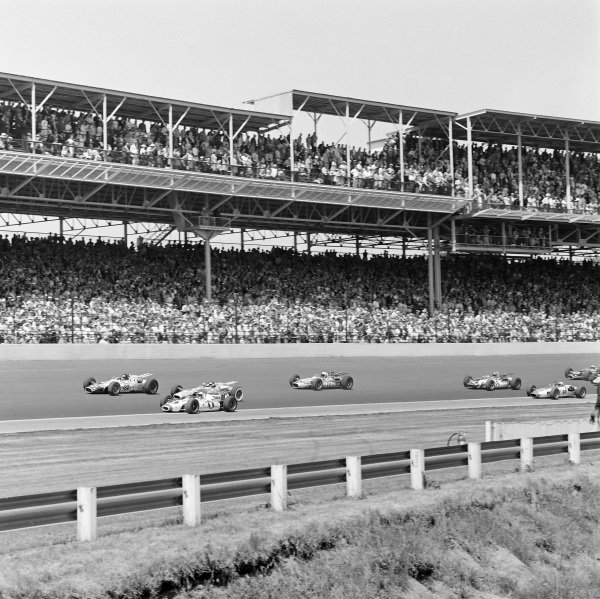 Mario Andretti, Al Dean, Hawk Ford, battles with Jim Clark, Lotus 38 Ford, and George Snider, Ansted-Thompson Racing, Lotus 38 Ford, at the start. They lead Gordon Johncock, Weinberger & Wilseck, Gerhardt Offenhauser, Lloyd Ruby, All American Racers, Eagle Mk2 Ford, Parnelli Jones, J. C. Agajanian, Shrike Offenhauser, and Don Branson, Bob Wilke, Gerhardt Ford.