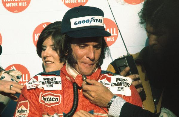 1974 United States Grand Prix East. Watkins Glen, New York, USA. 4th - 6th October 1974. Emerson Fittipaldi (McLaren M23-Ford), 4th position, portrait. New drivers world champion Emerson Fittipaldi celebrates taking his second world title.World Copyright: LAT Photographic. Ref: 74USA