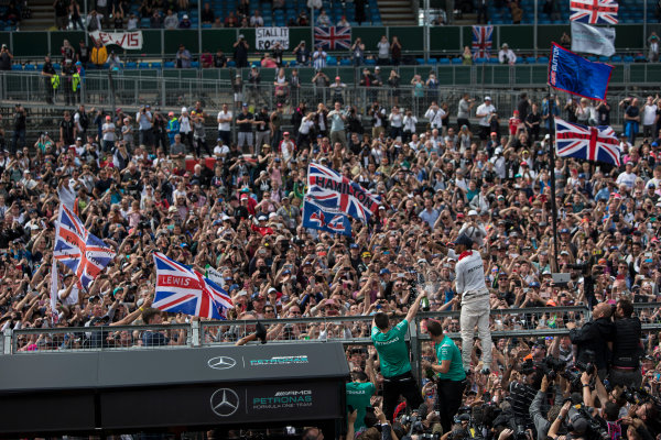 Silverstone, Northamptonshire, UK Sunday 10 July 2016. Lewis Hamilton, Mercedes AMG, 1st Position, celebrates victory at his home race with the fans. World Copyright: Ferraro/LAT Photographic ref: Digital Image _FER9086