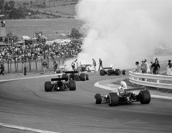 Cars stream past the fiery accident involving Mike Hailwood, Clay Regazzoni and Jacky Ickx on lap 3 South African GP, Kyalami, 3 March 1973