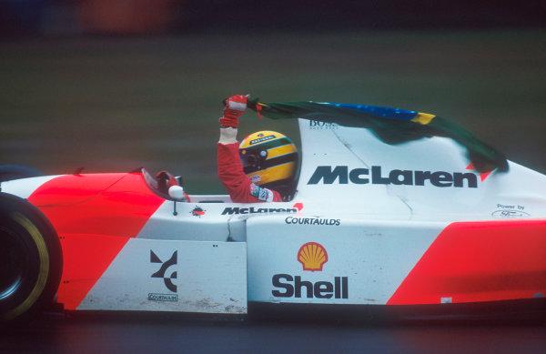 1993 European Grand Prix. Donington Park, England. 9-11 April 1993. Ayrton Senna (McLaren MP4/8 Ford) flies the flag of Brazil after an amazing drive to win the race. Ref-93 EUR 26. World Copyright - LAT Photographic