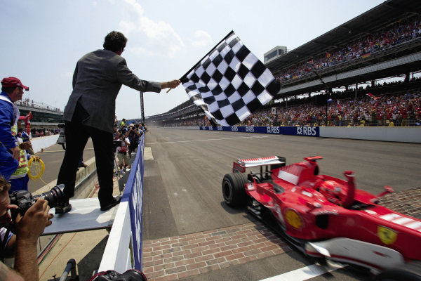 Michael Schumacher, Ferrari 248 F1 celebrates victory as he takes the chequered flag over the yard of bricks.