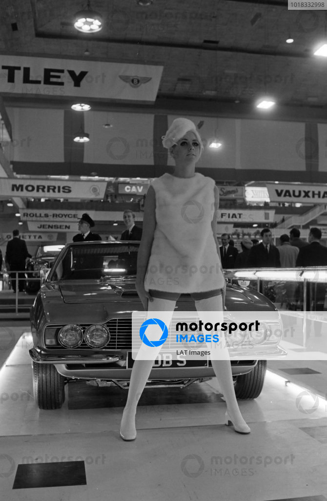 A model poses in front of an Aston Martin DBS