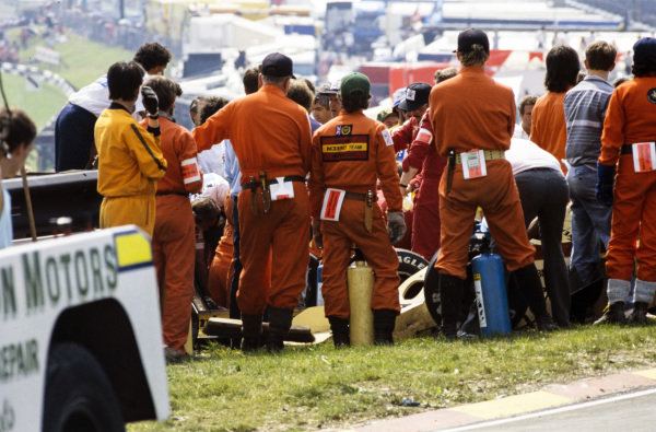 Marshals attend an Arrows A8 BMW, and Jacques Laffite, Ligier JS27 Renault, following a multi-car collision.