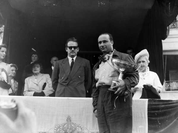 Juan Manuel Fangio, 1st position, on the podium with Prince Rainier.
