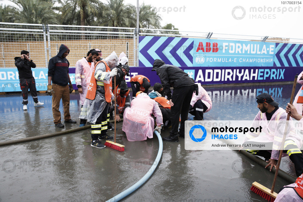 Marshals clear water from the track