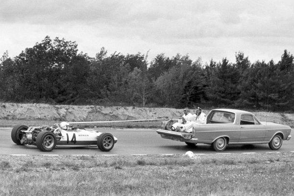 1966 United States Grand Prix.Watkins Glen, New York, USA.30/9-2/10 1966.Ronnie Bucknum (Honda RA273), retired, gets a tow back to the pits, action.Ref- B/W Print.World Copyright - LAT Photographic