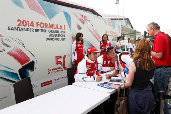 Silverstone, Northamptonshire, England. Saturday 5 July 2014. Fernando Alonso, Ferrari, and Kimi Raikkonen, Ferrari, sign autographs for fans. World Copyright: Andrew Ferraro/LAT Photographic. ref: Digital Image _FER0408