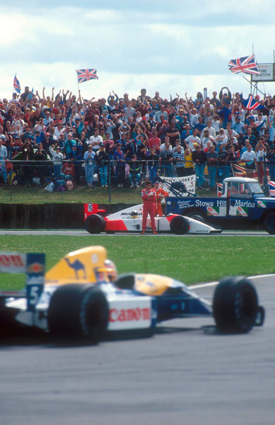 1992 British Grand Prix.Silverstone, England.10-12 July 1992.Ayrton Senna (McLaren MP4/7A Honda) watches Nigel Mansell (Williams FW14B Renault) drive on to 1st position from trackside after his retirement, due to a gearbox failure.Ref-92 GB 04.World Copyright - LAT Photographic