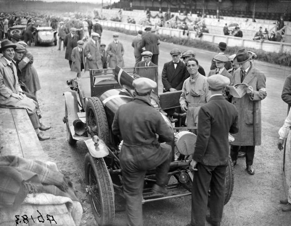 Sammy Davis (looking at camera, goggles round neck) stands next to the Bentley 3 Litre Speed he shares with Dudley Benjafield, in the pit area.