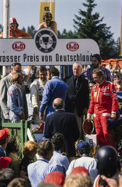 Winner Carlos Reutemann on the podium with Jacques Lafitte, 2nd position, and Niki Lauda, 3rd position. Harold Ertl congratulates Reutemann.