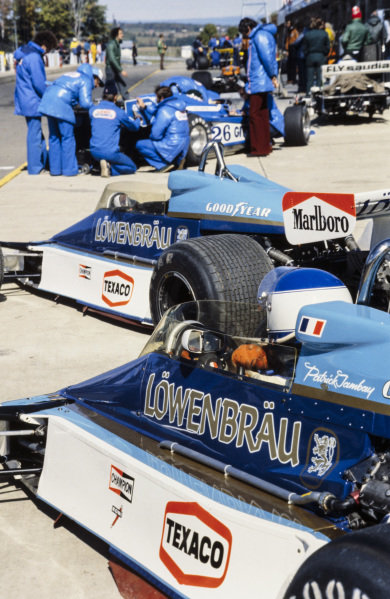 Patrick Tambay sits in the cockpit of his McLaren M26 Ford in the foreground as mechanics work on the rear of Jacques Laffite's Ligier JS9 Matra ahead.