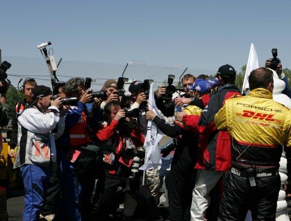 Romain Dumas (FRA) Penske Motorsports celebrates with the photographers. American Le Mans Series, Rd3, Mid-Ohio, USA, 21 May 2006. DIGITAL IMAGE