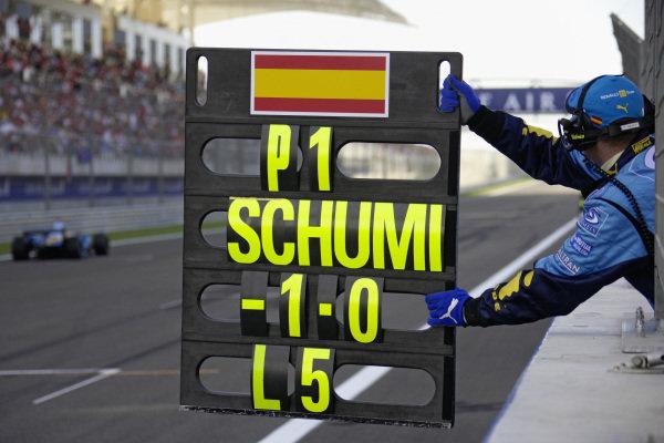 Fernando Alonso's pitboard showing Michael Schumacher 1 second behind.