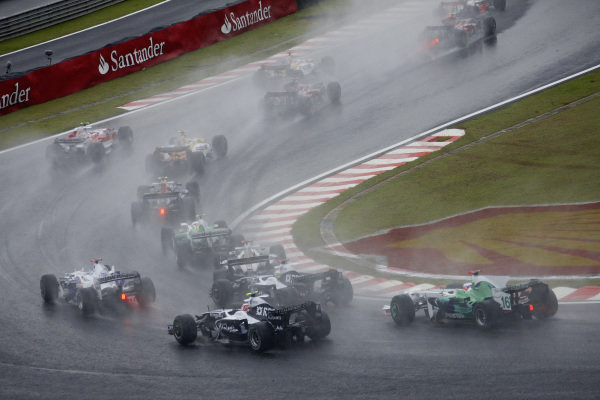 The field navigate the first chicane in the wet conditions at the start.
