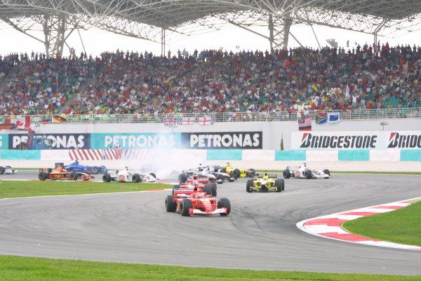 2001 Malaysian Grand Prix.Sepang, Kuala Lumpur, Malaysia. 16-18 March 2001.Michael Schumacher (Ferrari F2001) leads at the start of the race, as Ralf Schumacher (Williams FW23 BMW) spins.World Copyright - LAT Photographicref: 8 9MB DIGITAL IMAGE