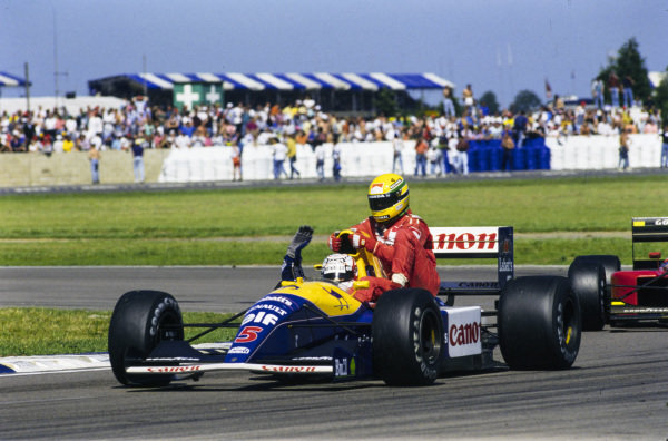 Nigel Mansell, Williams FW14 Renault, gives Ayrton Senna a ride back to Parc Ferme at the end of the race.