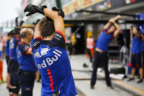 Toro Rosso mechanics warm up for pit stop practice
