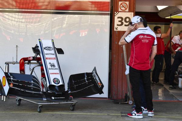 Kimi Raikkonen, Alfa Romeo Racing, examines a front wing