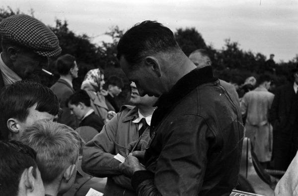 A driver signs autographs for fans.