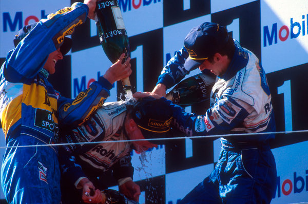 Estoril, Portugal.22-24 September 1995.Michael Schumacher (Benetton Renault) 2nd position and Damon Hill (Williams Renault) 3rd position give David Coulthard (Williams Renault) 1st position a champagne shower, for his maiden Grand Prix win on the podium.Ref-95 POR 03.World Copyright - LAT Photographic