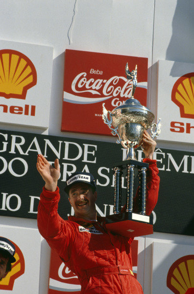 Jacarepagua, Rio De Janeiro, Brazil. 24-26 March 1989. Nigel Mansell (Ferrari) can bearly lift his trophy after his 1st position on his Ferrari debut, on the podium.  World Copyright - LAT Photographic