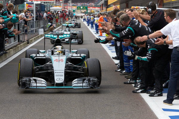 Spa-Francorchamps, Spa, Belgium. Sunday 23 August 2015. Lewis Hamilton, Mercedes F1 W06 Hybrid and Nico Rosberg, Mercedes F1 W06 Hybrid return the pits to the applause of their team after the race. World Copyright: Steve Etherington/LAT Photographic ref: Digital Image SNE22472