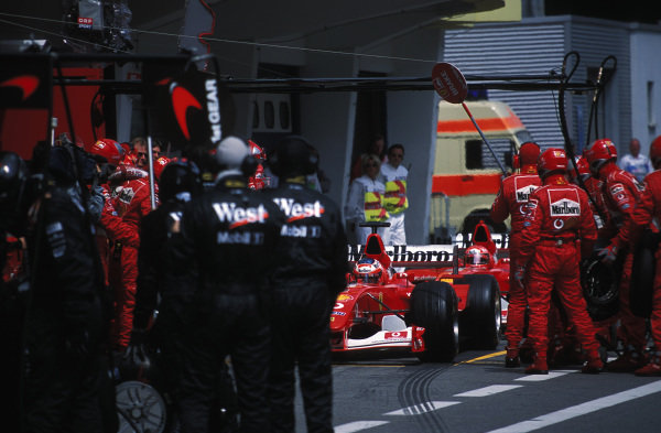 The Ferrari team double-stacks its drivers during pitstops, with Rubens Barrichello, Ferrari F2002, being serviced before Michael Schumacher.